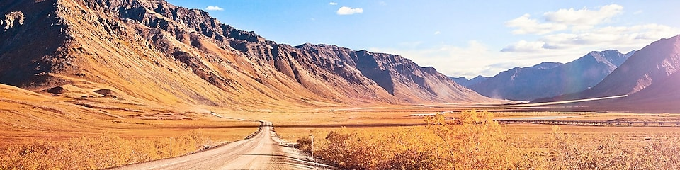 Empty dirt road surrounded by mountains