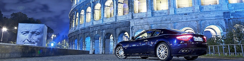 Car parked outside of the Colosseum in Rome at night